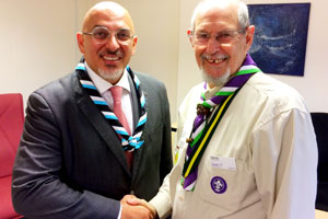 Nadhim Zahawi shaking hands with Tony Guy wearing a Stratford District necker
